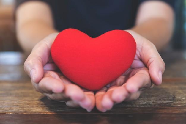 Immagine del primo piano delle mani che tengono un segno di cuore ...